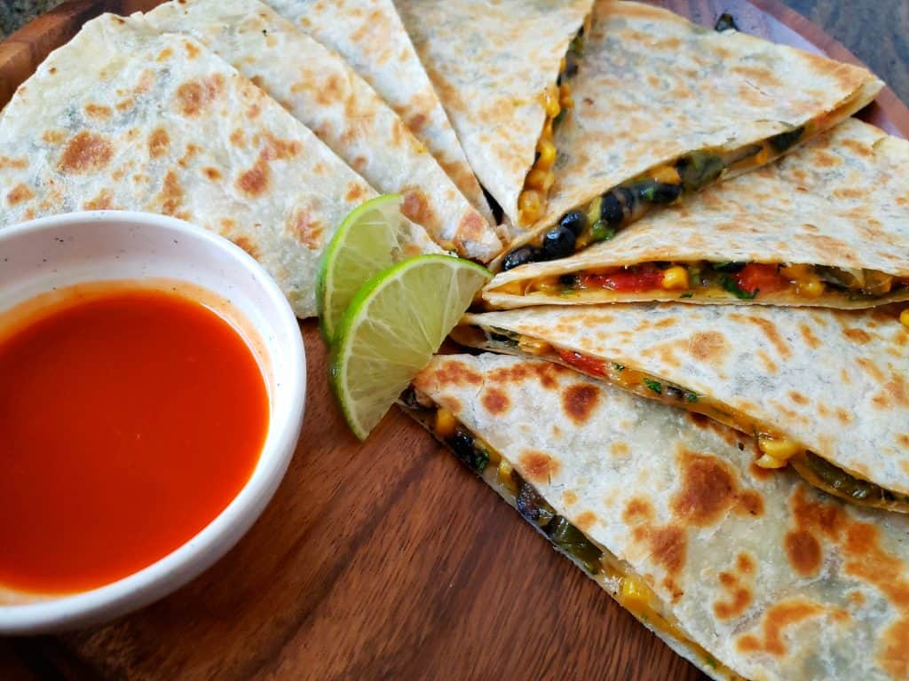 Appetizer plated vegetarian quesadilla wedges with hot sauce and lime wedges
