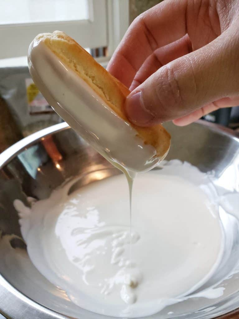 Dipping eclairs into white chocolate